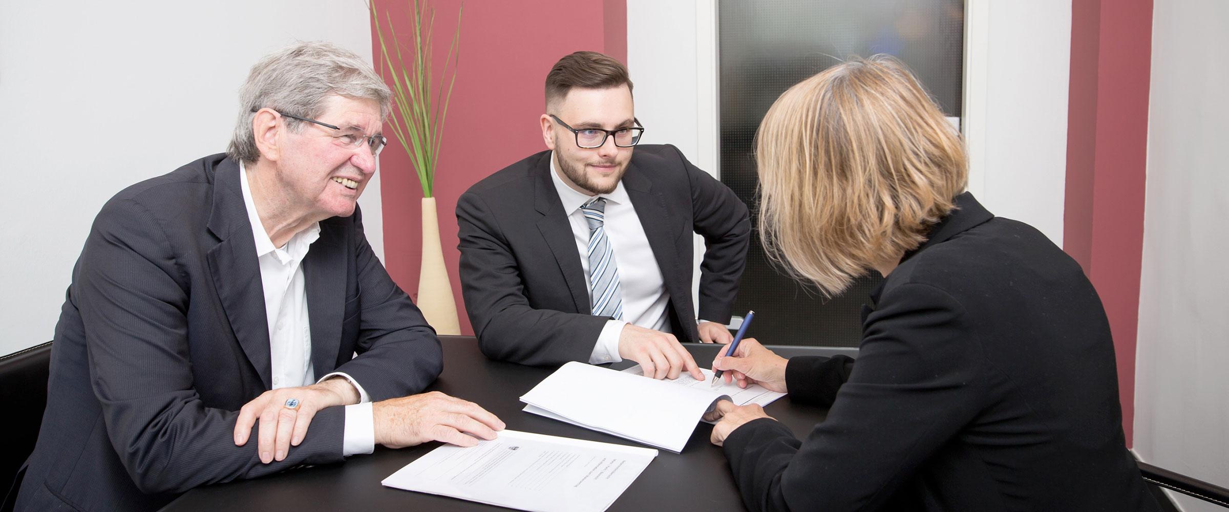 2 Polke und Partner Mitarbeiter sitzen einer Kundin gegenüber, die soeben Verkaufspapiere unterzeichnet.