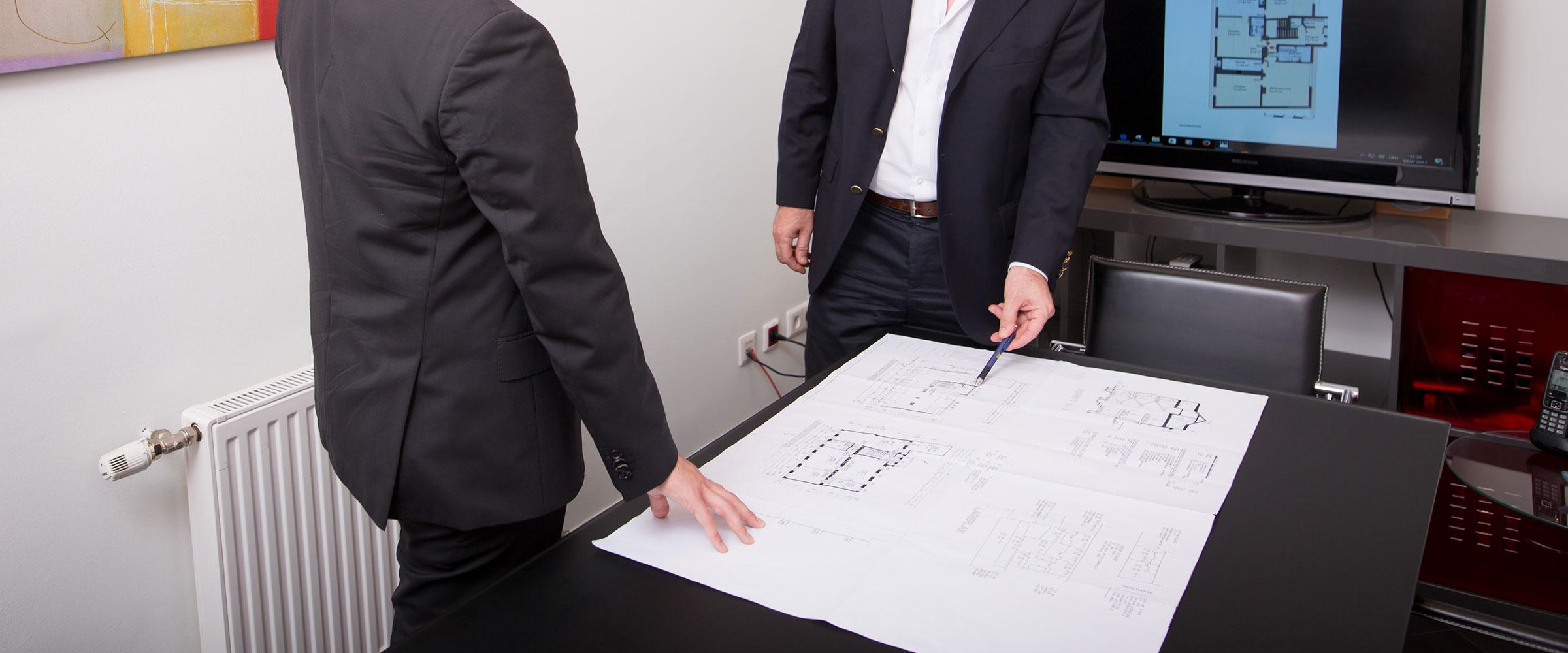 Zwei Herren stehend einem Tisch auf dem ein großer Plan ausgebreitet ist.