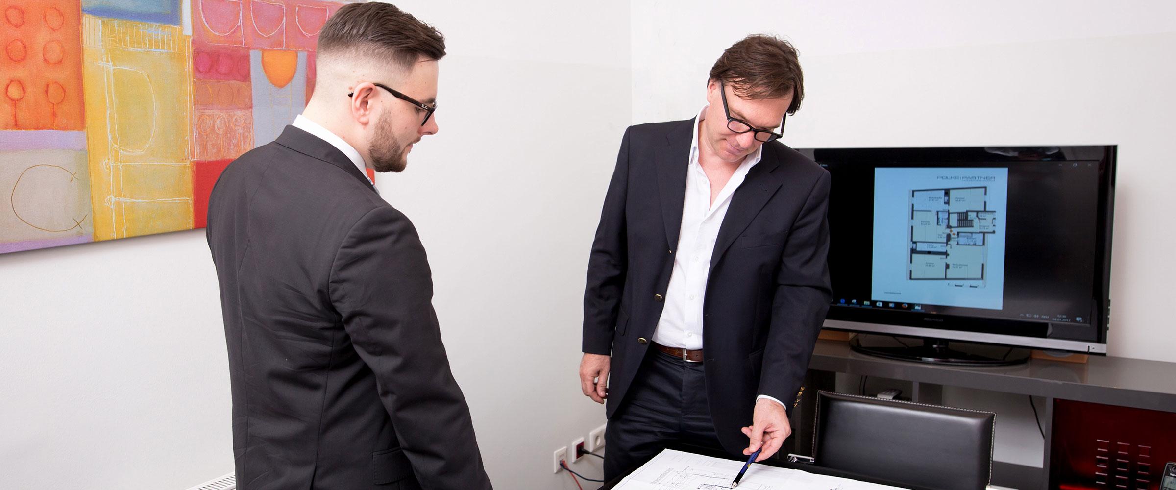 Stefan Polke im Gespräch mit einem Mitarbeiter; sie sehen sich Pläne an um ein Vermarktungskonzept zu entwickeln