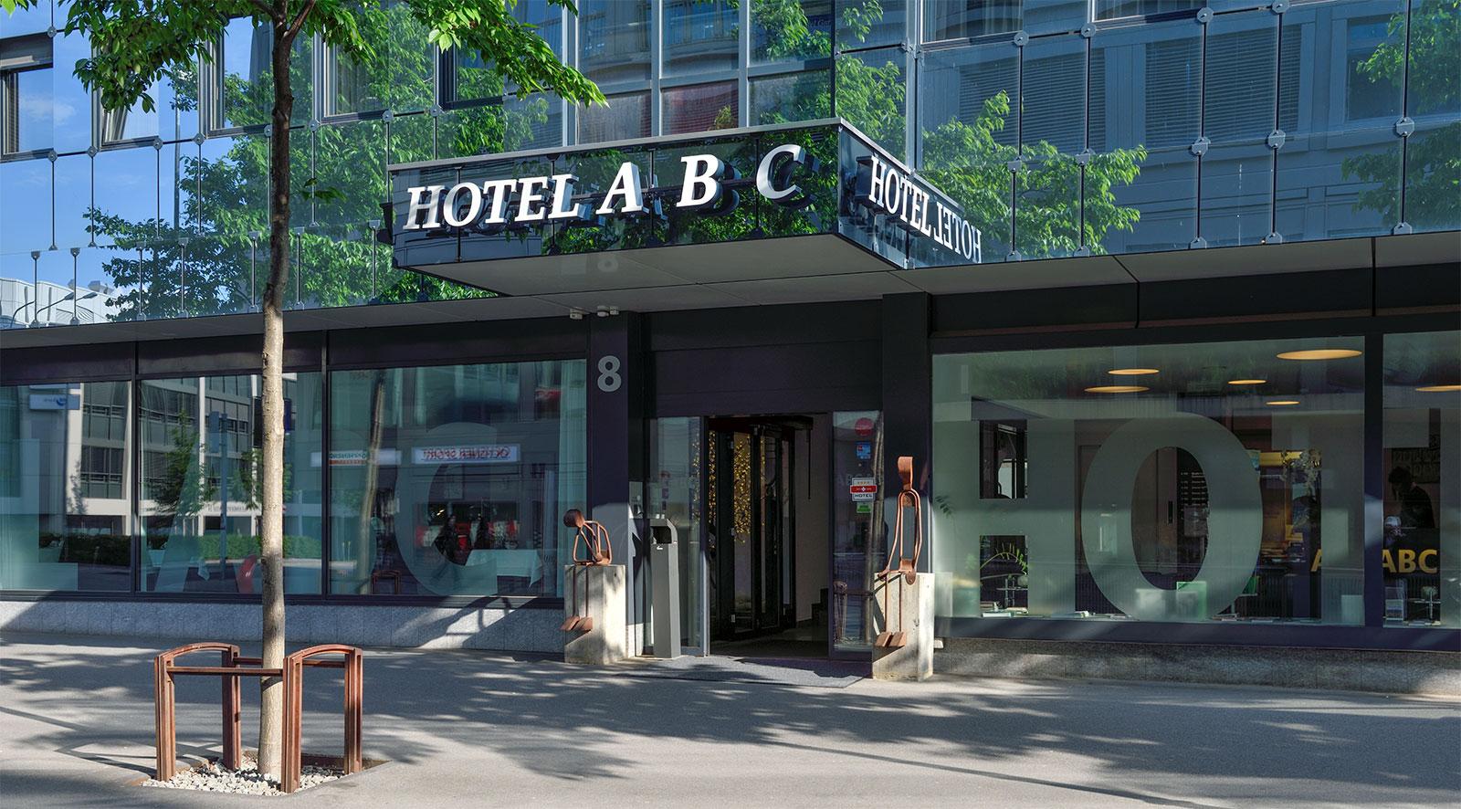 """Bild von einem Hotel-Eingang, Glasfasade; über dem Hotel steht """"Hotel A B C""""."""