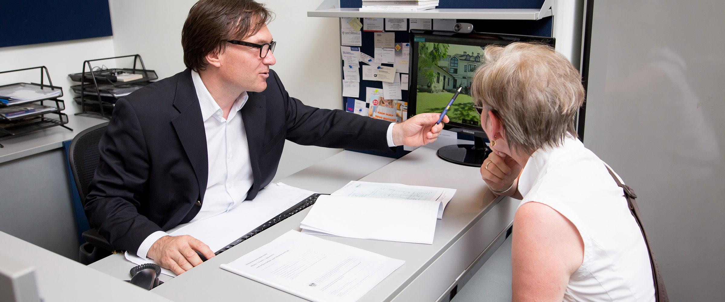 Stefan Polke beim Schreibtisch; gegenüber eine Kundin, der er ein Haus am Bildschirm präsentiert.