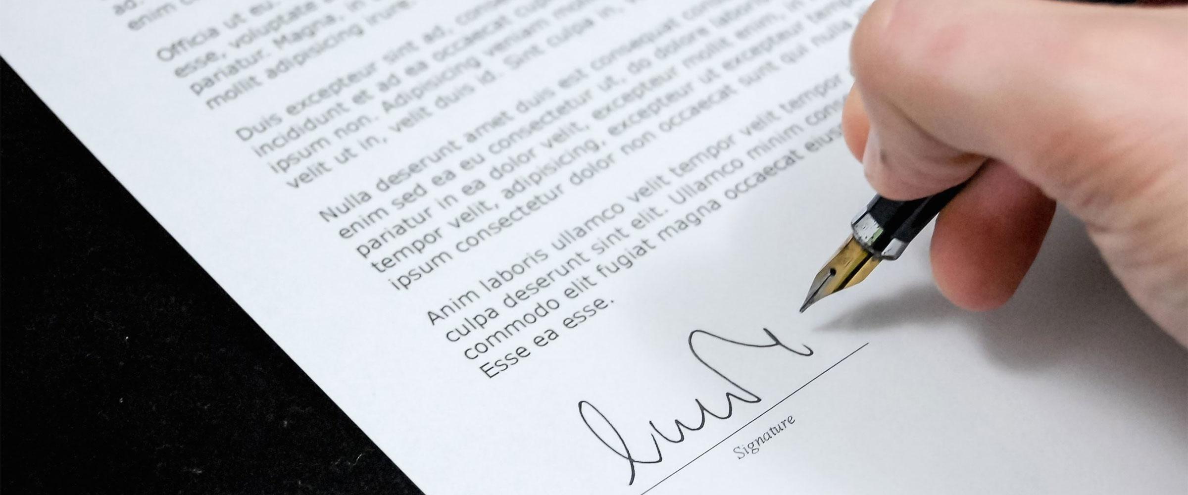 Eine Hand, die soeben mit einem Füllfederhalter einen Vertrag unterschreibt.