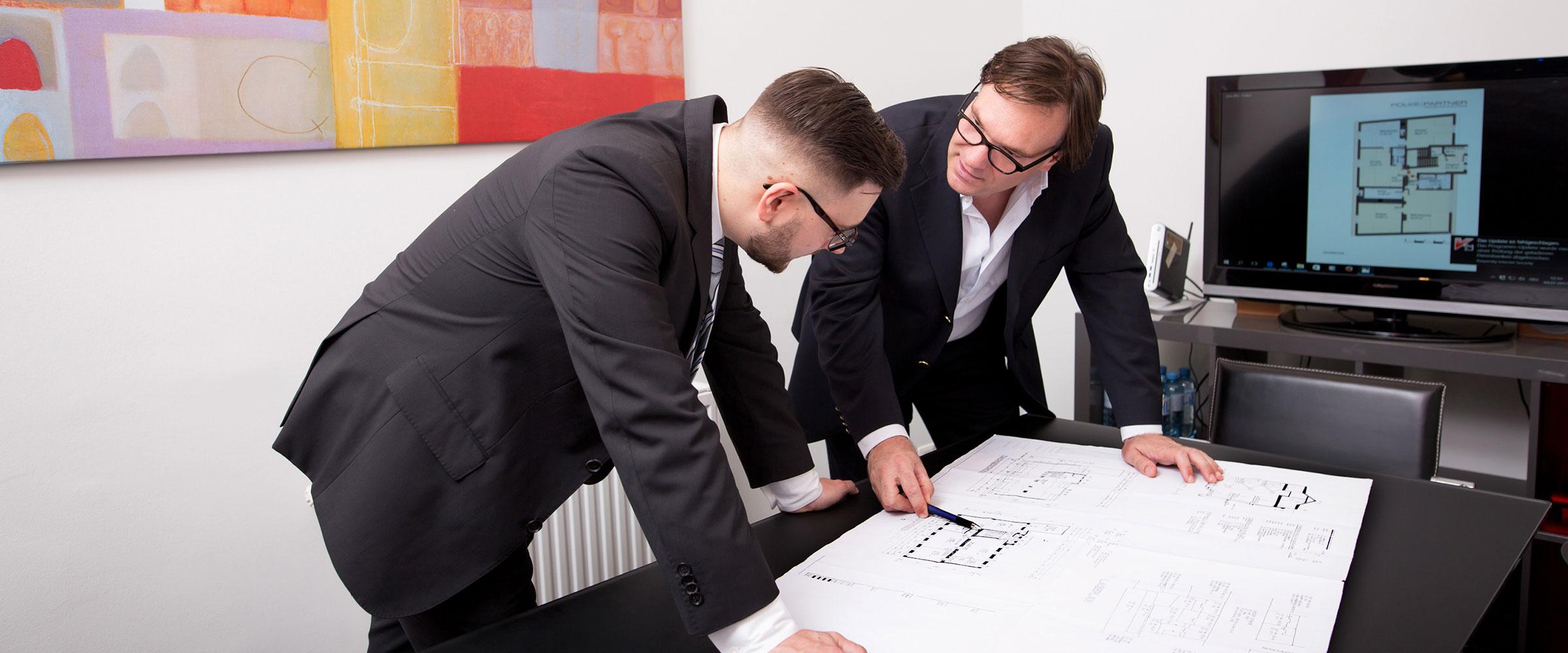 Stefan Polke bespricht mit Mitarbeiter einen Plan, der die Nutzraum-Fläche einer Immobilie zeigt.