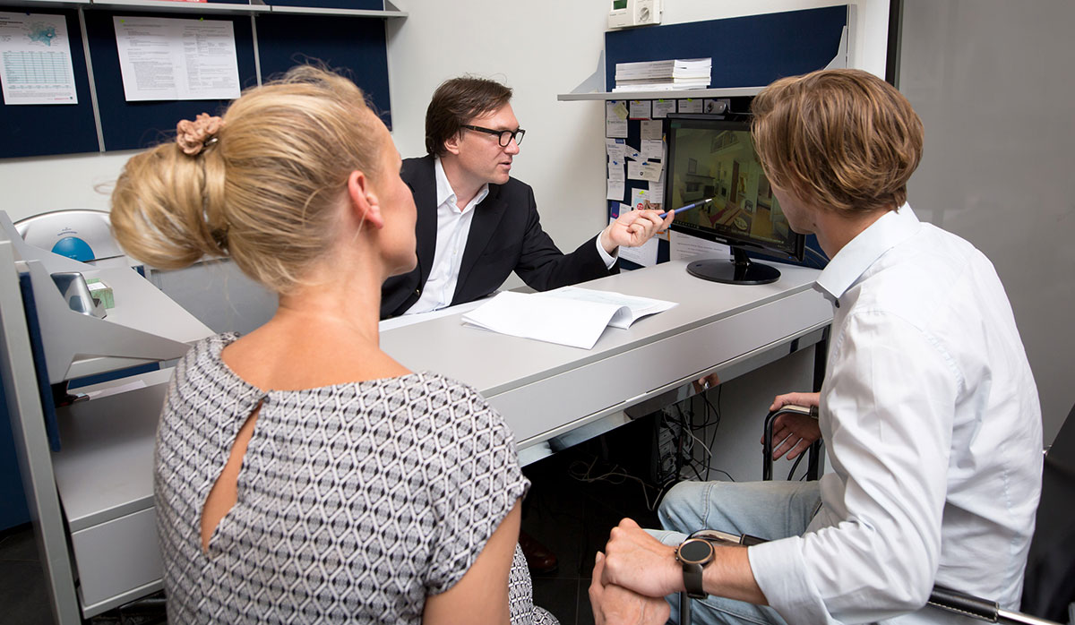 Stefan Polke im Beratungsgespräch mit einem jungen Paar, das eine Wohnung sucht.