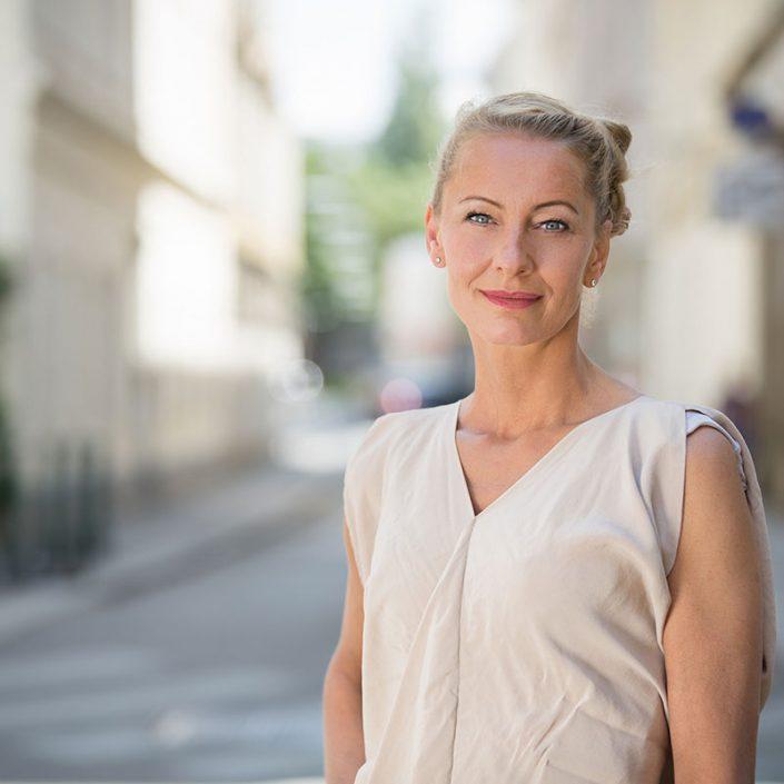Abbildung von Petranna Bayerl, blonde, aufgesteckte Haare, blaue Augen, weißes Shirt.