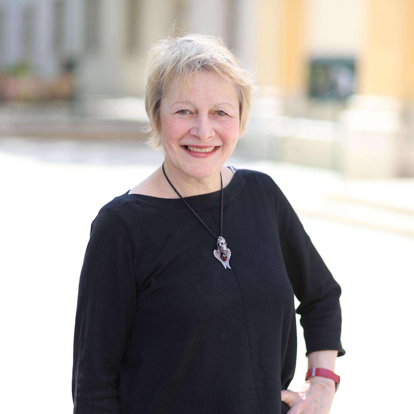 Abbildung von Architektin DI Maria Peer, kurze blonde Haare, weißes Shirt, Sichel förmige Halskette aus silber.