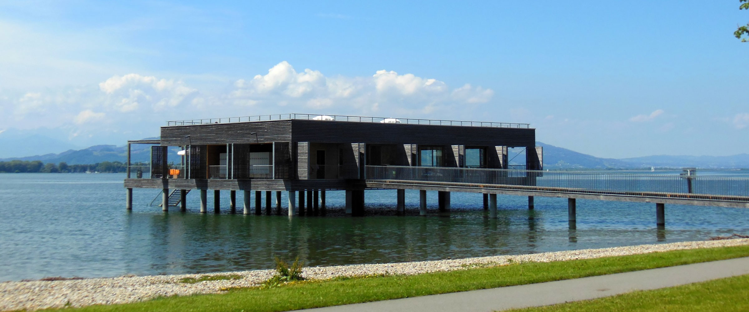 Ein großes Holzpfahlhaus im Plattform-Design in einem großen See; vom Ufer führt ein langer Steg zum Haus.