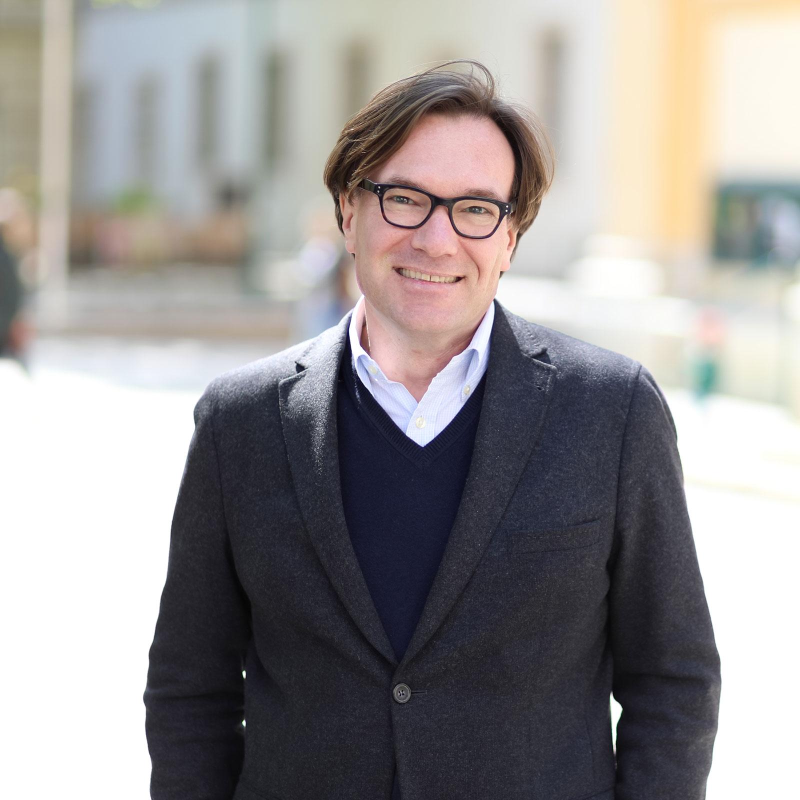 Abbildung von Stefan Polke mit Brille, Anzug und Hemd.